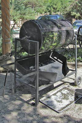 A photo of a chile roaster with tongs.