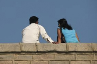 A photographic image of a man and woman sitting on a wall.