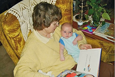 A photographic image of Mary reading a story to Baby Aiden.