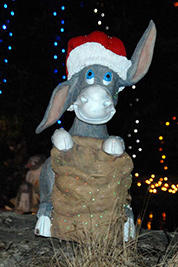 A photographic image of a statue of a donkey wearing a Santa hat.
