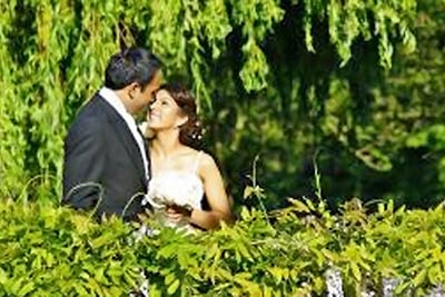 A photographic image of a bride and groom beneath a tree.