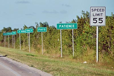 A photographic image of highway signs that emphasize patience.